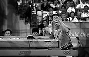 China's triple world champion Wang Liqin celebrates as he plays at the Beijing Olympics.
