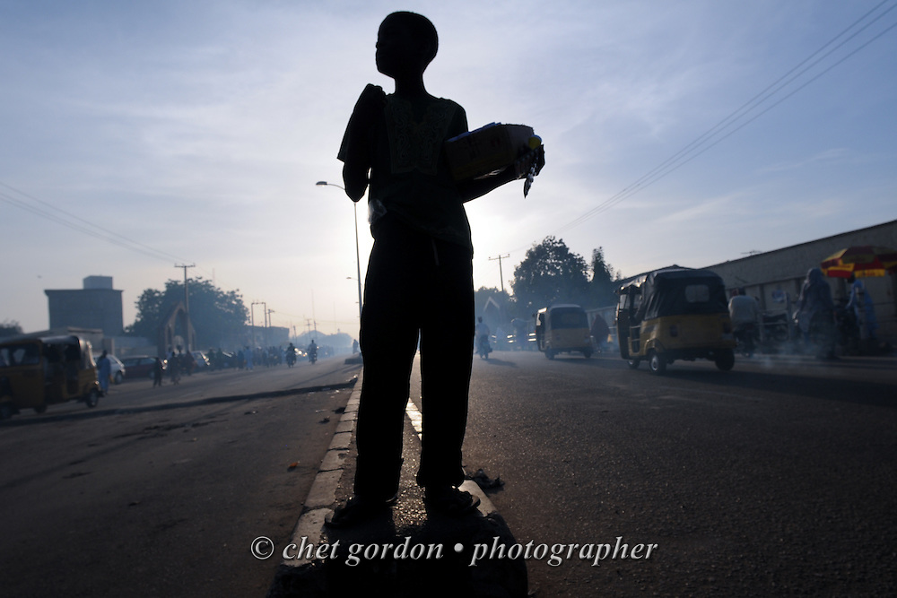 A boy pauses on a roadway divider as he sells candy to motorists along a busy street in Kano, Nigeria on Thursday evening, December 6, 2012.