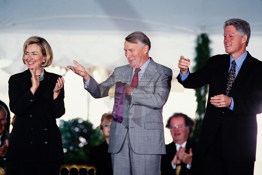 Journalist Robert MacNeil accepts the the National Medal of Arts on behalf of the MacDowell Colony from President Bill Clinton and First Lady Hillary Clinton during a ceremony on the South Lawn of the White House September 29, 1997 in Washington, DC.