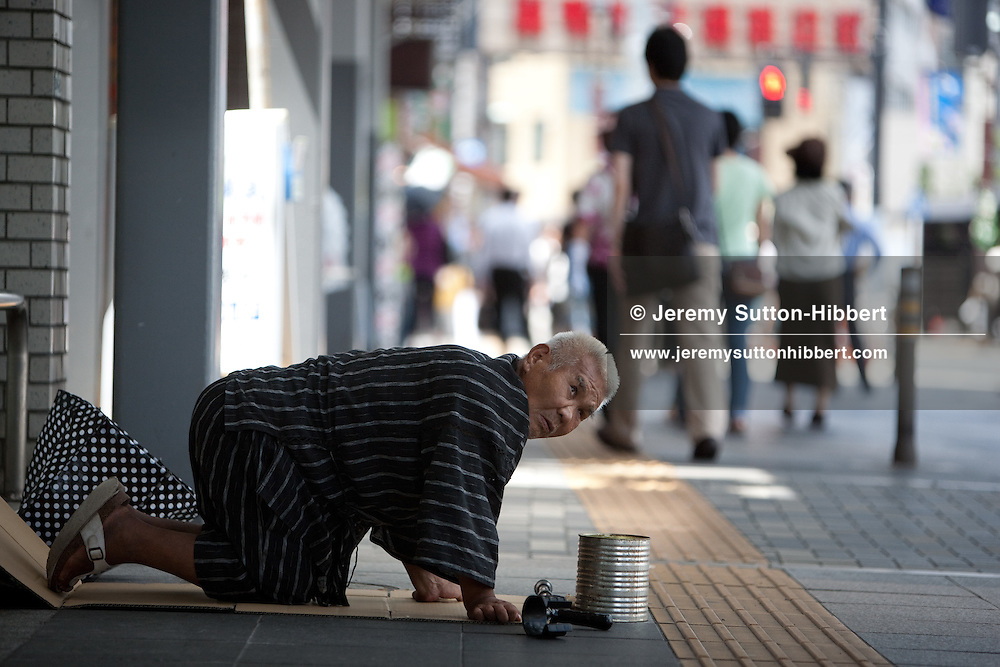 Elderly male pensioner kneels in the street begging for money in a shopping street in Sugamo district (a district favoured by old people for a temple they visit and shops catering to their needs) of Tokyo, Japan, Wednesday 11th August 2010. Japan has recently launched a nationwide search for  some missing elderly people, centenarains and 'city's oldest residents' who have moved address or have disappeared from known registrars. The discrepancies, and disapearances, came to light when officials updated public records of elderly citizens prior to a day in honour of the elderly.