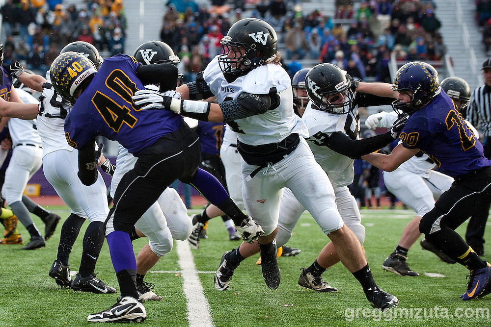 Vale junior Zac Jacobs looks for running room behind the blocks of Andrew Weber on Joey Knox and Michael Young on Hunter Knox during the first quarter of the Oregon 3A State Championship game at Kennison Field, Hermiston, Oregon, November 29, 2014. Vale defeated Harrisburg 45-19 to end the season with a 12-0 record and Vale's 11th state football title.<br />