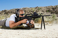 Man aiming machine gun at firing range