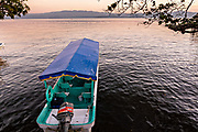 Aater taxi known as a Panga along the shore of Lake Catemaco at sunset in Catemaco, Veracruz, Mexico.  The tropical freshwater lake at the center of the Sierra de Los Tuxtlas, is a popular tourist destination and known for free ranging monkeys, the rainforest backdrop and Mexican witches known as Brujos.