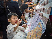 16 NOVEMBER 2013 - BANGKOK, THAILAND:  A youngster plays a lottery like game at the Wat Saket temple fair. Wat Saket is on a man-made hill in the historic section of Bangkok. The temple has golden spire that is 260 feet high which was the highest point in Bangkok for more than 100 years. The temple construction began in the 1800s in the reign of King Rama III and was completed in the reign of King Rama IV. The annual temple fair is held on the 12th lunar month, for nine days around the November full moon. During the fair a red cloth (reminiscent of a monk's robe) is placed around the Golden Mount while the temple grounds hosts Thai traditional theatre, food stalls and traditional shows.   PHOTO BY JACK KURTZ