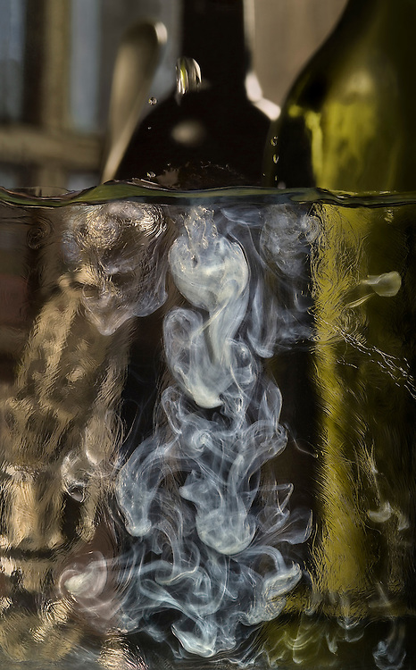 Louche #1. Photograph of absinthe being louched. The term refers to the dripping of chilled water into the absinthe. As the water is added, the mixture swirls mcreating the effect in the image. The end result is a beautiful opalescent mixture. Delicious