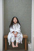 Young Girl wearing bathrobe Sitting on Bench by Bathtub