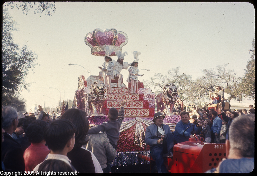 Revelers participate in the 1966 Mardi Gras parade in New Orleans, Louisiana. Revelers cheer as a float passes by.