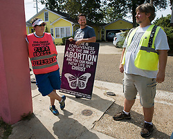 Pro-life activist Keith Dalton, 28, center, engages in a lively discussion with two pro-choice activists that volunteer as patient escorts, at the Jackson Women's Health Organization clinic,  on Tuesday August 19, 2014, in Jackson, Mississippi. This is the only clinic in the entire state that performs abortions. (Photo © Jock Fistick)