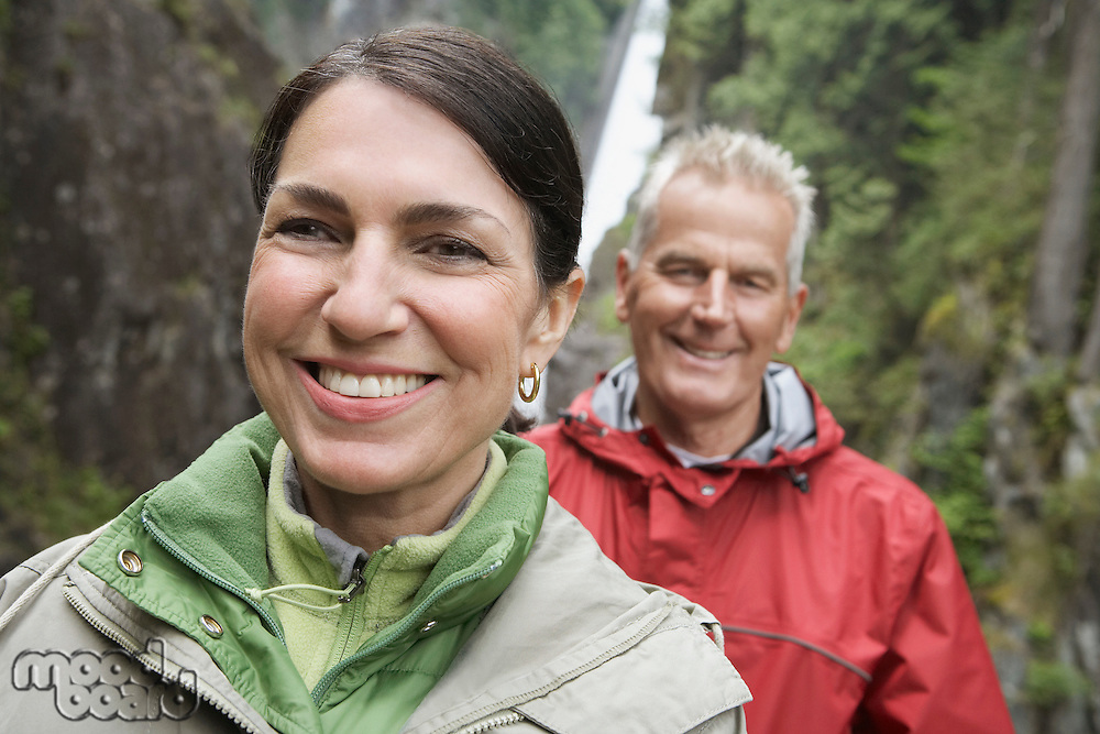 Portrait of man and woman smiling waterfall in background