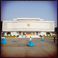 Women in traditional dress in front of the Kim Jong-il Gift Museum in Pyongyang, North Korea.