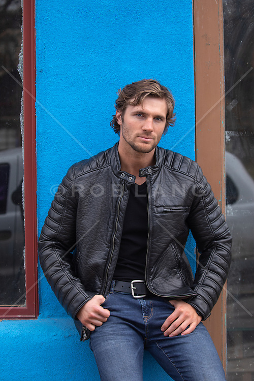 portrait of a good looking man in a leather jacket against a wall