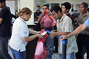 A deportee collects his belongings at the Migration Office in Guatemala City's La Aurora Airport after having been deported from the United States. Each week, fourteen flights arrive at La Aurora Airport from the U.S. carrying 135 deportees per airplane. Mostly men, the would-be migrants spend an average of two months at U.S. detention centers before they are sent back. From January 1st to May 17th, 2013, there have been 18,073 people deported back to Guatemala. Guatemala City, Guatemala. May 17, 2013.