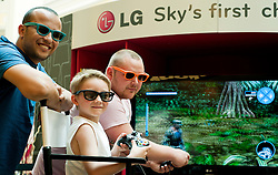 Kai Higgins (aged 6) tries his had at 3D gaming with Carl O'Roarke (right) and Nino Ouni (Left) in LG's Life's Good Lounge interactive living room installation which was in Meadowhall over the bank holiday ..22 April 2011.Images © Paul David Drabble