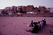 """Shibam, desert storm. In the foreground men praying at sunset. Declared Unesco World Heritage, the old city of Shibam is called the """"Manhattan of the desert"""" and is one of the most celebrated Arabic Islamic cities built in traditional style. A collection of nearly 500 skyscrapers built with mud bricks and 5-7 stores high."""