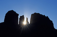 The rising sun is filtered through Cathedral Rock in Sedona, Arizona.