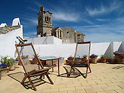 The rooftop patio at La Casa Grande, a small inn in the town of Arcos de la Frontera, Andalusia, Spain. The Church of St. Peter looms in the distance.
