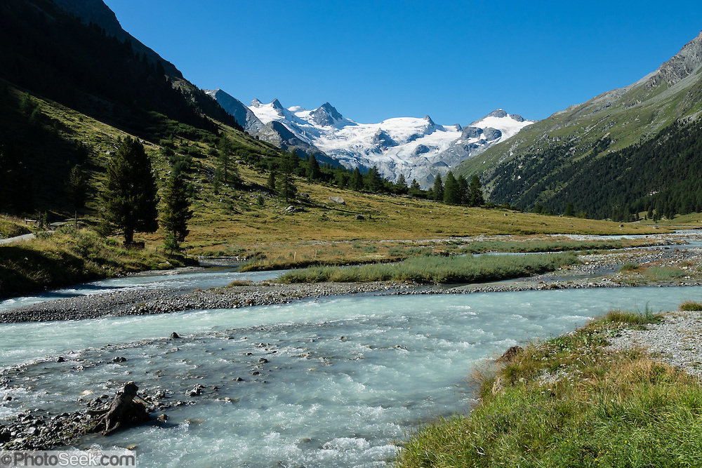 """The icy Bernina Range rises above Ova da Roseg river valley, near Pontresina, Switzerland, in the Bernina Alps, Europe. Roseg Glacier flows from Piz Glüschaint (3594 m/11,791 ft). Val Roseg is in the Swiss canton of Graubünden (or Grisons / Grigioni / Grischun); the lower Roseg Valley is in Pontresina, whereas the upper valley is in an exclave of Samedan Municipality. Hike from Pontresina up Roseg Valley to Fuorcla Surlej for stunning views of Piz Bernina and Piz Roseg, finishing at Corvatsch Mittelstation Murtel cable car. Walking 14 km, we went up 1100 meters and down 150 m. Optionally shorten the hike to an easy 4 km via round trip lift. The Swiss valley of Engadine translates as the """"garden of the En (or Inn) River"""" (Engadin in German, Engiadina in Romansh, Engadina in Italian), and is part of the Danube basin."""