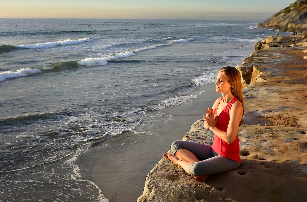 Woman meditating at the Terramar Cliffs in Carlsbad, CA at Sunset.