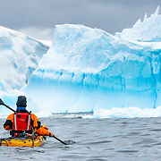 A kayaker geared up in cold-water gear paddles towards large blue icebergs near Melchior Island on the western side of the Antarctica Peninsula.