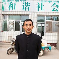 """GAOBEIDIAN, 7.NOV. 2014 : Han Deqiang, Manager der Farm des Rechten Weges, vor einem Propaganda Schild, das uebersetzt """" harmonische Gesellschaft"""" bedeutet."""