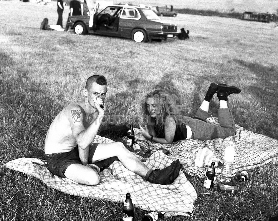 Couple sitting on blankets, drinking beer in field, man shirtless, Free Party, 2000's,