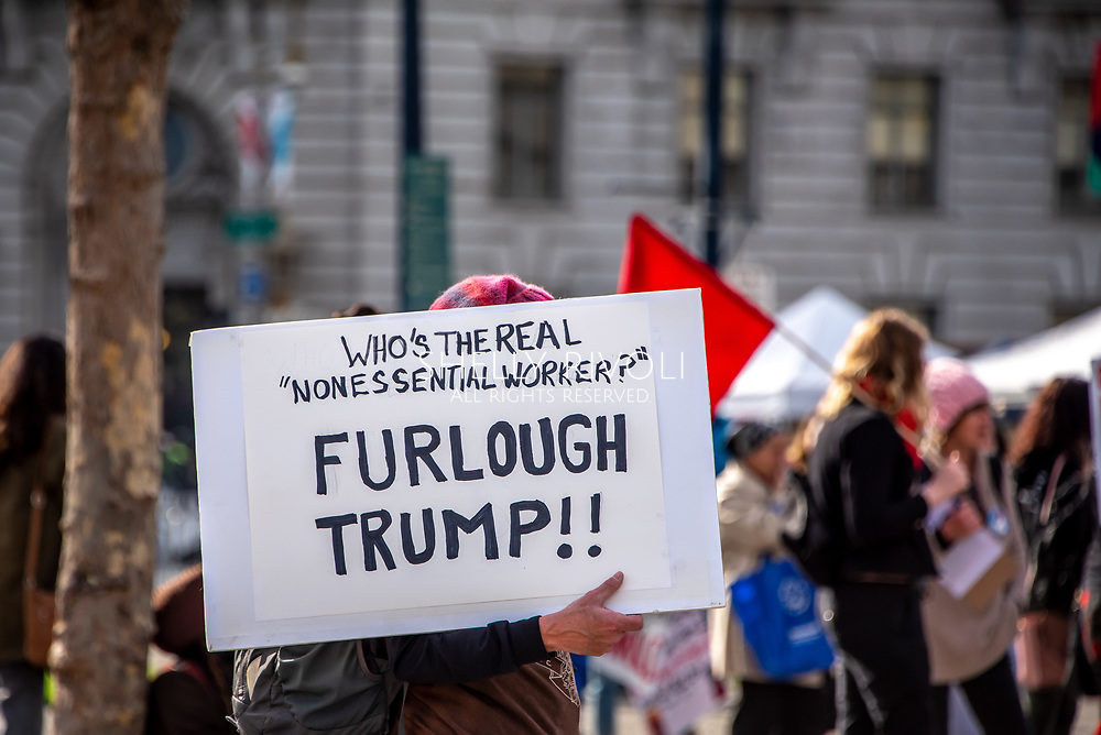 "San Francisco, USA. 19th January, 2019. The Women's March San Francisco begins with a rally at Civic Center Plaza in front of City Hall. A protester carries a sign through the plaza questioning, ""Who's the real 'nonessential worker'? Furlough Trump!"" Credit: Shelly Rivoli/Alamy Live News"