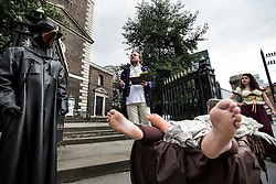 © Licensed to London News Pictures. 04/09/2015. London, UK. An actor dressed as author Daniel Defoe (centre) reads an extract from his from 'A Journal of the Plague Year' outside St Boltoph without Aldgate Church. Actors in traditional costumes took part in a procession from Minories (near the Tower of London) to St Botolph's in which they dragged a cart with 'plague victims' and yelled 'bring out your dead' to passing members of public. This is to mark 350 years since the plague pit at church was completed. It also marks the opening of the Great Plague Festival which runs until September 6th. Photo credit : James Gourley/LNP