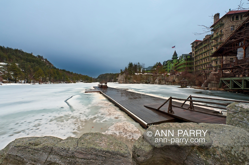NEW PALTZ - MARCH 14: Lake Mohonk seen beyond boulders at shore, with view of long wood pier, mountains and Mohonk Mountain House on overcast winter morning of March 14, 2010 at New Paltz, New York, USA. For Editorial Use Only.