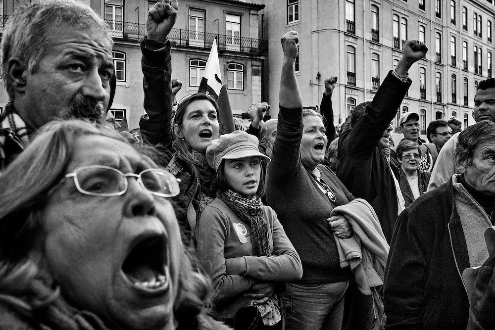 People sing the Portuguese national anthem near the cordon of riot police officers by the stairway of the Congress during a demonstration to marking the European coordinated general strike in Lisbon, Portugal, on November 14, 2012. Around 1.4 million people are currently unemployed in Portugal, and only 370,000 of them have receiving monthly social support from the government, leaving around 1 million people without the benefit. Over youths, unemployment rates is breaking records reaching 39% in the third quarter of the year, or equivalent to more than 175,000 people. The official unemployment rate in Portugal is currently on 15.7%, a bit away from the highest European rate in Spain, with 25.8%, followed by Greece with 25.1% of jobless. Photo by Mauricio Lima for The New York Times