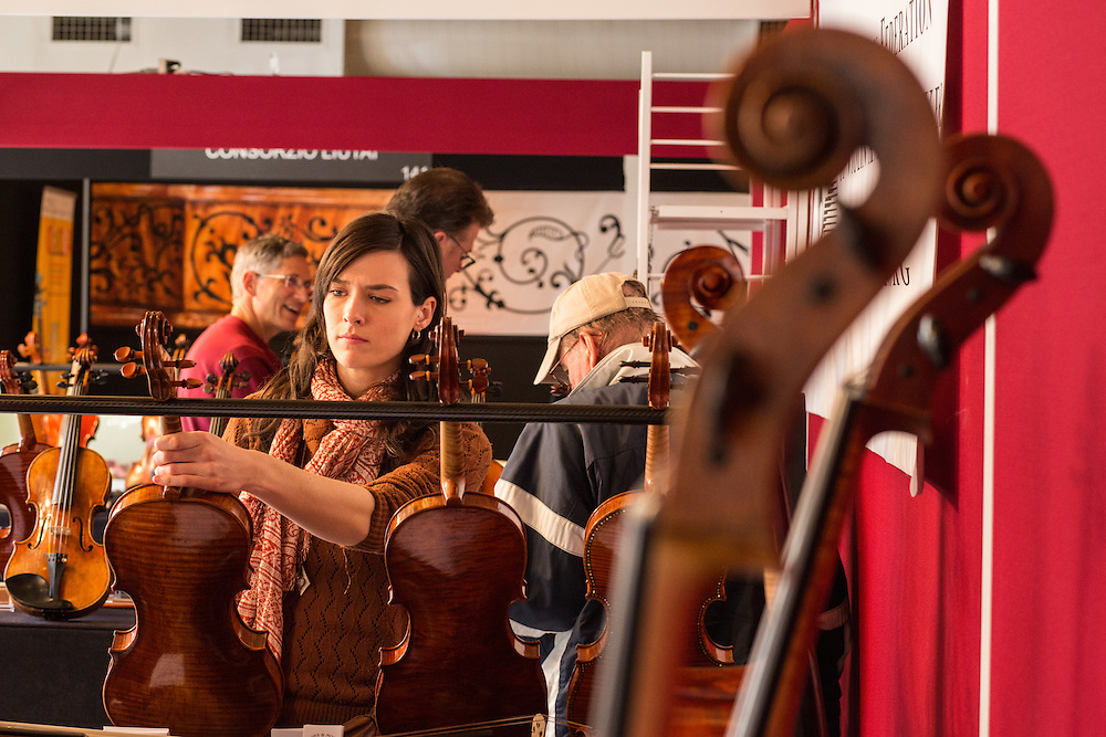 A woman looks at a violin displayed by the American Federation of Violin and Bow Makers.