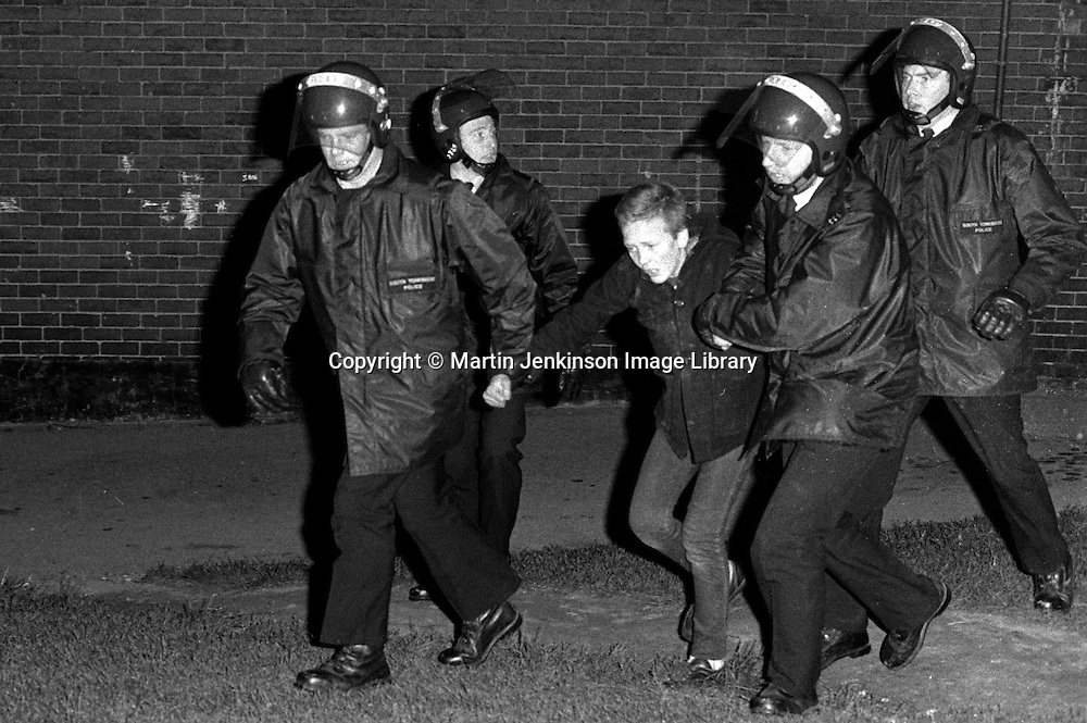 Police wearing riot helmets arrest a young boy in Grimethorpe during the 1984-85 Miners Strike.16/10/1984