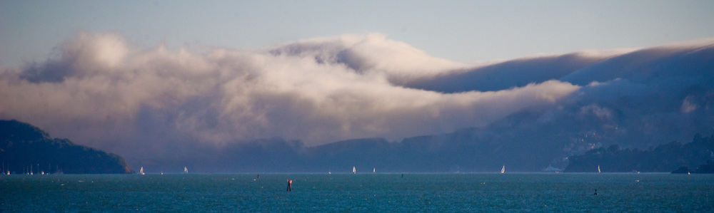 A thick cottony wave of fog spills over hills into San Francisco bay on a chilly July afternoon