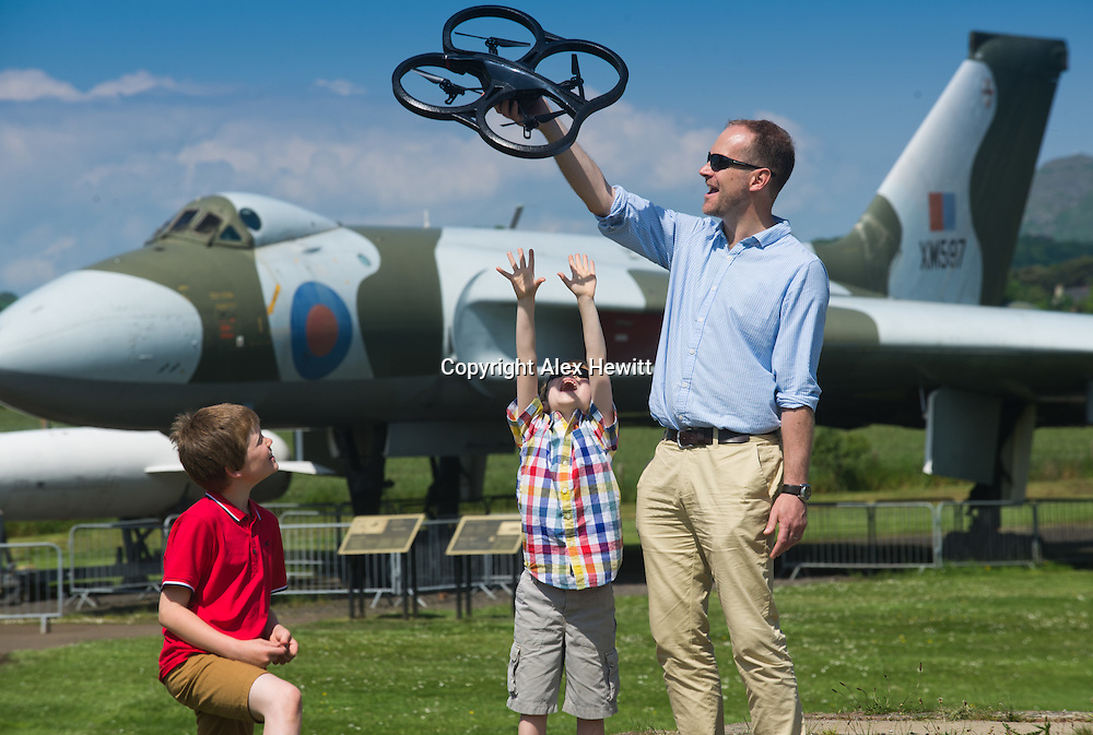 Brian McCall and his two sons Bruce (9) and Fraser (6) get close up to a Parrot AR Drone 2.0 as they look forward to celebrating Father&rsquo;s Day at the Robots Live event at the National Museum of Flight on Sunday 15th June.  The event will feature a talk and demo on Drones: Robots of the Skies, along with robot battles, fun activities and science demonstrations on a range of robotic action<br />