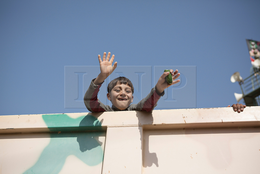 Licensed to London News Pictures. 11/11/2016. Mosul, Iraq. A young Iraqi refugee from Mosul waves from an Iraqi Army truck as he and others prepare to leave the city's Hay Intisar district for the safety of a refugee camp. Hay Intisar district was taken four days ago by Iraqi Security Forces (ISF) and, despite its proximity to ongoing fighting between ISF and ISIS militants, many residents still live in the settlement without regular power and water and with dwindling food supplies.<br /> <br /> The battle to retake Mosul, which fell June 2014, started on the 16th of October 2016 with Iraqi Security Forces eventually reaching the city on the 1st of November. Since then elements of the Iraq Army and Police have succeeded in pushing into the city and retaking several neighbourhoods allowing civilians living there to be evacuated - though many more remain trapped within Mosul.  Photo credit: Matt Cetti-Roberts/LNP