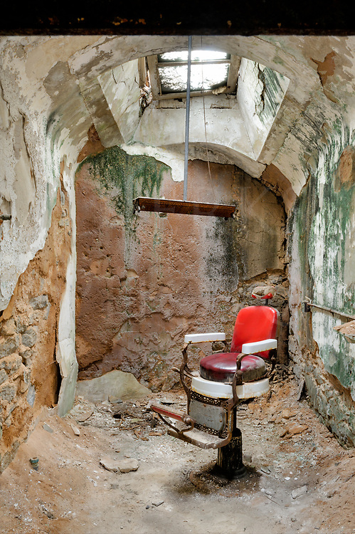 Barber shop and chair in a decaying prison cell among the ruins of the Eastern State Penitentiary in Philadelphia.