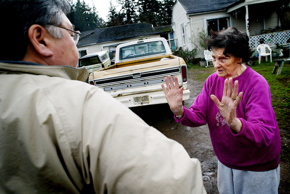 February 28, 2004 - Ann Isaksen, 83 (right), makes a plea to Victor Unkow (left) for more time to clean up her property maintenance code violations on her property located at SE 131st and Long in SE Portland. Victor Unkow is one of 10 housing and nuisance inspectors for the City of Porltand, Oregon. Victor was doing a checkback on the code violations and stated that Ann's property looked much better, and that he would work with Ann and give her more time to make sure that she was in compliance with city code. When Victor tells Ann that he will give her the extra time she needs to clean it up, she says: &quot;I can hug you for that, but I know it's against the law.&quot; <br /><br />Keywords : news 2004, property maintenance code, city of portland, city inspectors, housing inspector.