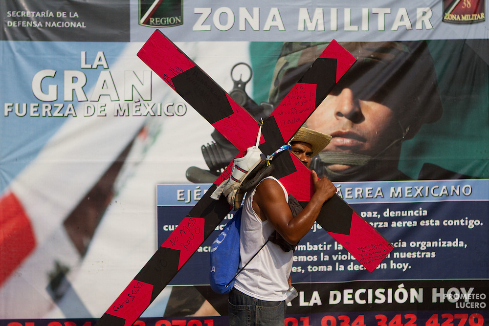 "A central american migrant carries a cross during the ""Viacrucis migrante"" in front of the  38A Military Zone, on April 6th, 2012. (Photo: Prometeo Lucero)"