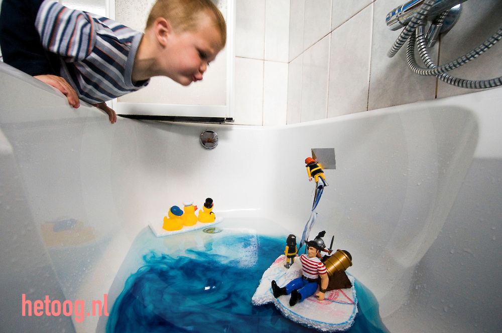 een kleuter speelt met een zelf gemaakt zeilbootje in bad