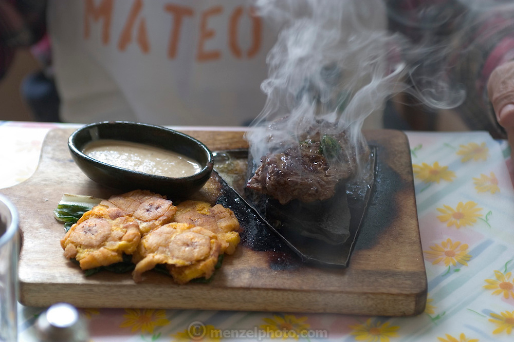 Close up of steak cooked to order in an upscale restaurant outside Quito, served with mushroom gravy and banana fritters. Ecuador. (Supporting image from the project Hungry Planet: What the World Eats)
