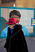 An elderly lady walks past the hoarding featuring the face of an NHS Staff Nurse employed at University College London, on 25th January 2018, in London, England.