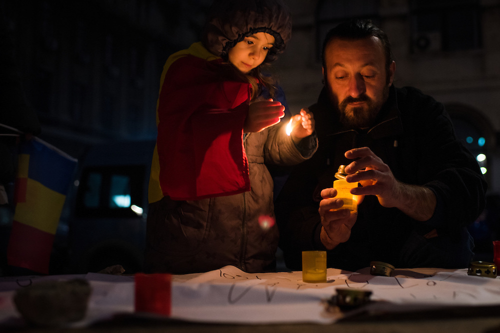 A father and daughter light candles in University Square on November 7, 2015 in Bucharest, Romania.