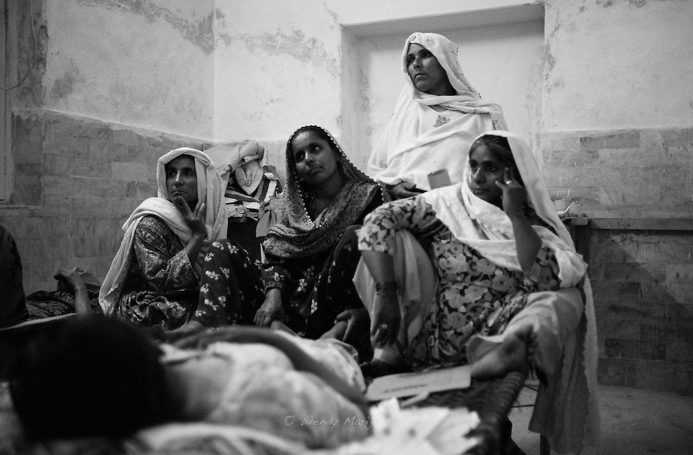 Female family members sit on the bed surrounding a patient that is waiting to undergo surgery during the surgical camp visiting their village. <br /> The high number of pregnancies, not having access to sufficient maternal care and lack of female doctors causes many problems with the womb in these remote areas later on. Suffering for years, these women finally get help by having a hysterectomy. Thari Mirwah, Pakistan, 2010