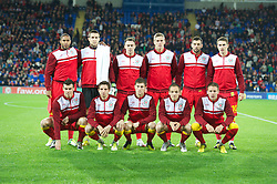 CARDIFF, WALES - Friday, October 12, 2012: Wales players players line up for a team group photograph before the Brazil 2014 FIFA World Cup Qualifying Group A match against Scotland wearing pink ribbons for missing five-year girl from Machynlleth April Jones at the Cardiff City Stadium. Back row L-R: captain Ashley Williams, goalkeeper Lewis Price, Darcy Blake, Steve Morison, Joe Ledley, Aaron Ramsey. Front row L-R: Gareth Bale, Joe Allen, Ben Davies, David Vaughan, Chris Gunter. (Pic by David Rawcliffe/Propaganda)