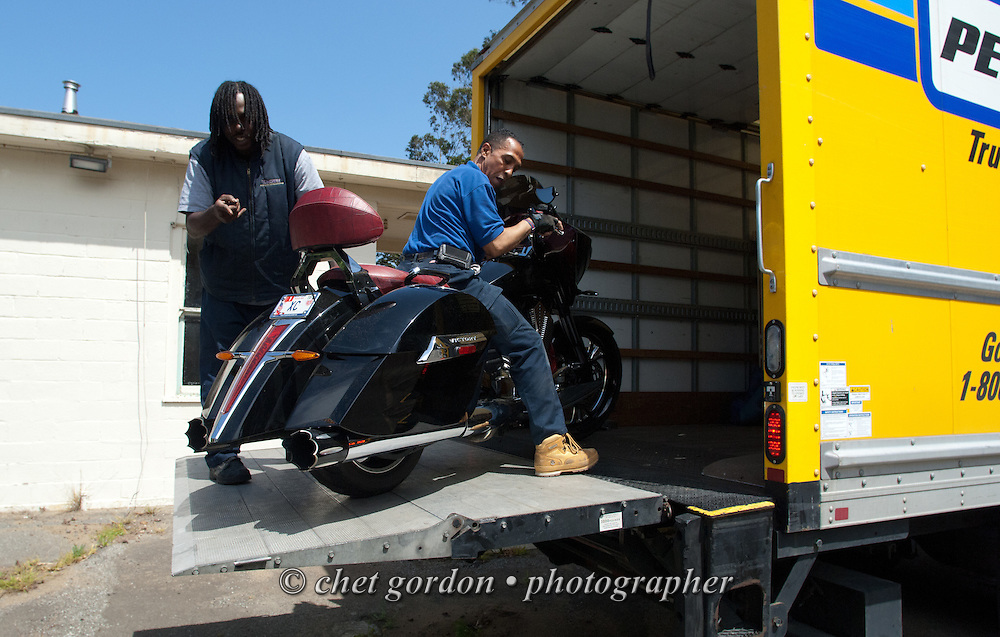 Over the road driver Jose Williams (right) guides a custom motorcycle onto the tail lift of a delivery truck in San Francisco, CA on Wednesday, April 22, 2015. Williams, a cross country trucker with a national household moving company, made several delivery stops in central California's Bay Area during the week with loads from Virginia originating on April 16th.  © Chet Gordon/THE IMAGE WORKS