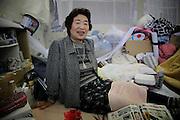Onagawa - Waka SUZUKI - Centre de réfugiés Undôjô sôgô taikukan - Juin 2011<br /> Waka Suzuki vit au centre de réfugiés avec son mari. Tous deux ont perdu leur maison et leur magasin qui se trouvaient à Onagawa et attendent un logement proposé par le gouvernement. Elle m'évoque son histoire et me parle de ses souvenirs et désirs [...] .« Pour le futur, j'ai plein de rêves » lance-t-elle. « Dabord, je veux voyager comme avant ! » Elle sort des photographies panoramiques de ses voyages qu'elle a pu retrouver dans les décombres. Elle parle de Singapour, d'Osaka ou de son séjour préféré à Kyoto lors de la fête de Gion. Elle les passe et repasse en silence. Puis sa gorge se noue en disant à nouveau : « oui, j'ai beaucoup de rêves »..Ces rêves dont elle parle sont inaccessibles et en deviennent douloureux. Le passé existe sous quelques images retrouvées, les photographies permettent alors de s'évader quelques instants. Mais, la réalité de ce présent difficile revient vite faire surface. Les photos du passé renvoient alors à ce qui fut à jamais perdu. Le choc est tel que pour longtemps, toutes projections futures en deviennent inabordables.