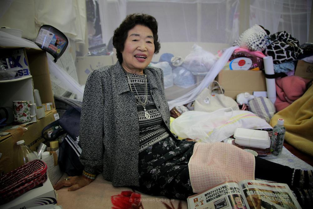 Onagawa - Waka SUZUKI - Centre de r&eacute;fugi&eacute;s Und&ocirc;j&ocirc; s&ocirc;g&ocirc; taikukan - Juin 2011<br /> Waka Suzuki vit au centre de r&eacute;fugi&eacute;s avec son mari. Tous deux ont perdu leur maison et leur magasin qui se trouvaient &agrave; Onagawa et attendent un logement propos&eacute; par le gouvernement. Elle m'&eacute;voque son histoire et me parle de ses souvenirs et d&eacute;sirs [...] .&laquo; Pour le futur, j'ai plein de r&ecirc;ves &raquo; lance-t-elle. &laquo; Dabord, je veux voyager comme avant ! &raquo; Elle sort des photographies panoramiques de ses voyages qu'elle a pu retrouver dans les d&eacute;combres. Elle parle de Singapour, d'Osaka ou de son s&eacute;jour pr&eacute;f&eacute;r&eacute; &agrave; Kyoto lors de la f&ecirc;te de Gion. Elle les passe et repasse en silence. Puis sa gorge se noue en disant &agrave; nouveau : &laquo; oui, j'ai beaucoup de r&ecirc;ves &raquo;..Ces r&ecirc;ves dont elle parle sont inaccessibles et en deviennent douloureux. Le pass&eacute; existe sous quelques images retrouv&eacute;es, les photographies permettent alors de s'&eacute;vader quelques instants. Mais, la r&eacute;alit&eacute; de ce pr&eacute;sent difficile revient vite faire surface. Les photos du pass&eacute; renvoient alors &agrave; ce qui fut &agrave; jamais perdu. Le choc est tel que pour longtemps, toutes projections futures en deviennent inabordables.