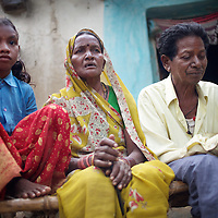 Amar Singh Patel (right) outside the family home with his wife, Sona Bai; and  grandaughter, Jaymati (age 11)...Amar Singh Patel, age 60 owns owns 5 acres of land, 1.5 of which is irrigated. He lives in Rathkhandi village, Bilaspur District, Chhattisgarh State with his wife Sona Bai, their daughter and son-in-law and four grandchildren...On this irrigated land, Amar Singh's family cultivate rice using the SRI technique together with a small vegetable plot. The remaining 3.5 acres are leased out to share-croppers. Amar Singh was introduced to SRI by Oxfam partners Jan Swasthya Sahyog (JSS) and began growing rice using this technique in 2007...Amar Singh's land did not always produce enough food for his family to eat. When Amar Singh was a young man, he and his family had to eat wild flowers to survive. They also had to sell their cattle, buy clothing on credit and migrate in search of work...The JSS introduced SRI to Amar Singh and others in his village. SRI is an organic system of intensively growing rice that can double crop yields double. ..Using SRI, Amar Singh and his family produce enough rice for all of their annual needs from only 1.5 acres of land. They now never go hungry...By using SRI Amar Singh never has to spend money on expensive chemicals which degrade the soil. SRI also uses less seed. With fewer inputs Amar Singh has made savings and invested these in his farm. Last year he purchased a new bullock cart. And Amar Singh's grandchildren no longer have to work the land when they should be at school as he did when he was a child. ..The JSS have recruited Amar Singh to advocate for SRI and teach other farmers the benefits of this system of agriculture. ..Photo: Tom Pietrasik.Chhattisgarh, India.November 2012