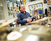 General Manager Clarence Berry plays a ukulele at Allegro Music in Fremont, California, on April 16, 2014. (Stan Olszewski/SOSKIphoto)