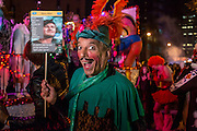 """New York, NY - 31 October 2015. A man in heavy makeup, wearing a green Robin Hood costume, carries a sign that says """"Mary Man"""", and advertising that he's looking for merry men."""