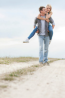 Happy young man giving piggyback ride to woman on trail at field